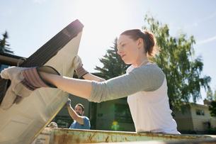 Couple placing door in dumpster home improvement project outdoorsの写真素材 [FYI02307267]