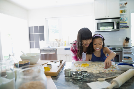 Mother and daughter using star cookie cutters on dough baking in kitchenの写真素材 [FYI02307309]