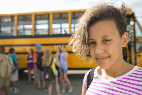 Portrait of little girl standing against school busの写真素材 [FYI02307315]