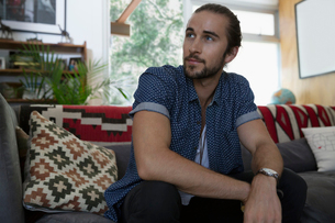 Pensive man looking away on living room sofaの写真素材 [FYI02307334]