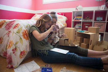 Girls making jewelry on bedroom floorの写真素材 [FYI02307364]