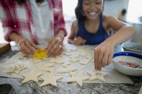 Mother and daughter using star cookie cutters on dough baking in kitchenの写真素材 [FYI02307392]