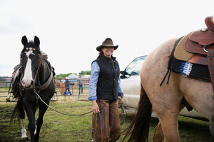 Portrait smiling female cattle rancher with horsesの写真素材 [FYI02307402]