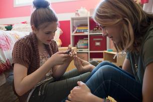 Girls making jewelry in bedroomの写真素材 [FYI02307420]