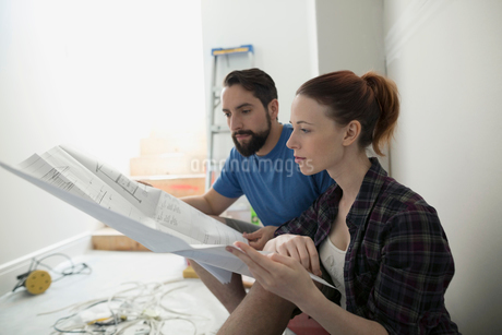 Couple reviewing blueprints for home improvement projectの写真素材 [FYI02307442]