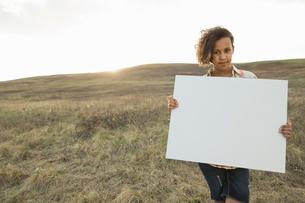 Portrait of schoolgirl holding blank signboard on fieldの写真素材 [FYI02307612]