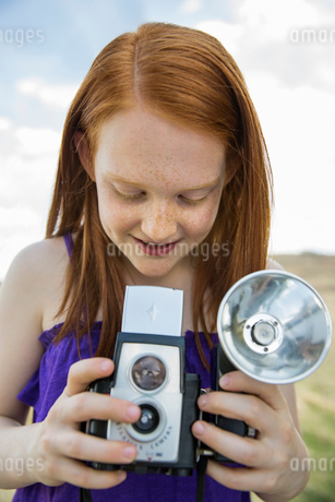 Smiling girl looking at vintage camera during field tripの写真素材 [FYI02307617]
