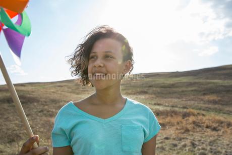 Schoolgirl looking at pinwheel on fieldの写真素材 [FYI02307624]