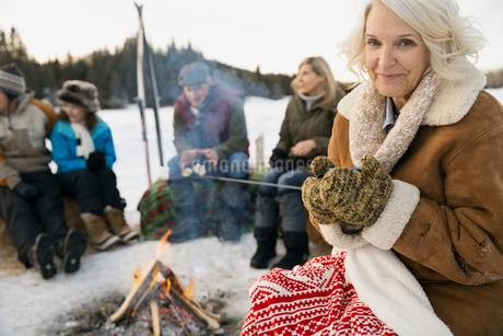 Portrait of smiling woman sitting by bonfire in winterの写真素材 [FYI02307701]