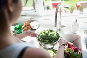 Woman washing green beans in colander at kitchen sinkの写真素材 [FYI02307745]