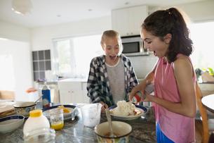Girls spraying whipped cream on pancake in kitchenの写真素材 [FYI02307860]