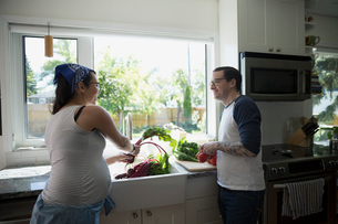 Pregnant couple washing vegetables at kitchen sinkの写真素材 [FYI02307949]