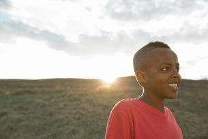 Smiling schoolboy looking away at fieldの写真素材 [FYI02308003]