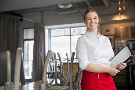 Portrait of confident waitress with menus in bistroの写真素材 [FYI02308018]