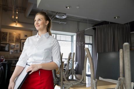 Confident waitress with menus in bistroの写真素材 [FYI02308257]