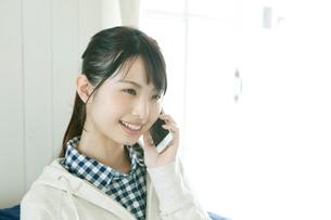 ソファに座って電話をする若い女性の写真素材 [FYI02308260]