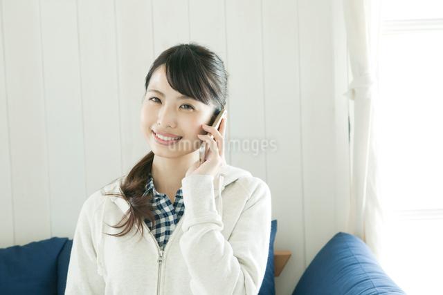 ソファに座って電話をする若い女性の写真素材 [FYI02308306]