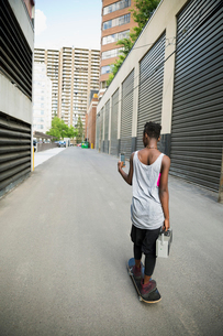 Cool young woman skateboarding with boom box and texting in urban alleyの写真素材 [FYI02308431]