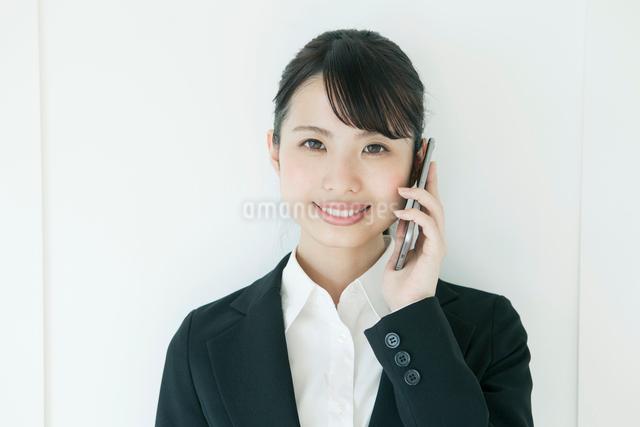 電話中のスーツ姿の若い女性の写真素材 [FYI02308434]