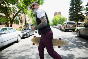 Hipster man with tattoos and coffee holding skateboard crossing streetの写真素材 [FYI02308435]