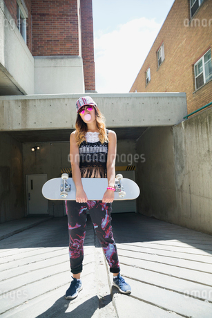 Portrait cool young woman holding skateboard at urban parking garage entranceの写真素材 [FYI02308450]