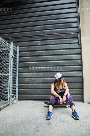 Cool young woman sitting on skateboard in urban alleyの写真素材 [FYI02308451]