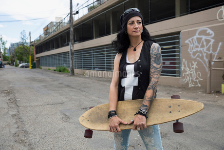 Portrait cool mature woman holding skateboard in urban alleyの写真素材 [FYI02308454]