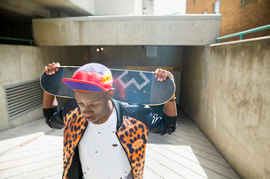 Cool young man holding skateboard at urban parking garage entranceの写真素材 [FYI02308455]
