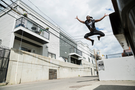 Exuberant young man jumping in urban alleyの写真素材 [FYI02308459]
