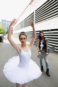 Portrait ballerina and cool skateboarder in urban alleyの写真素材 [FYI02308490]