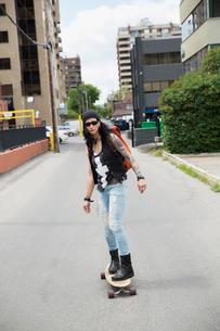 Cool mature woman skateboarding in urban alleyの写真素材 [FYI02308529]