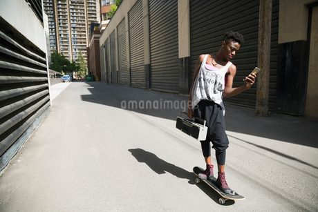 Cool young woman skateboarding with boom box and texting in urban alleyの写真素材 [FYI02308553]
