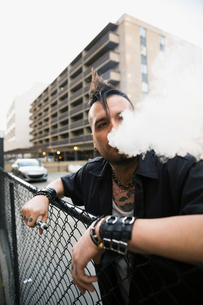 Cool man with mohawk smoking electronic cigarette at urban fenceの写真素材 [FYI02308568]