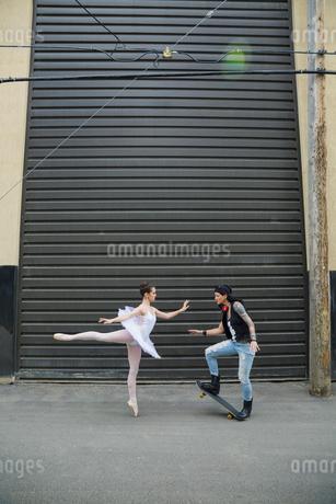 Dancing ballerina and cool skateboarder in urban alleyの写真素材 [FYI02308577]