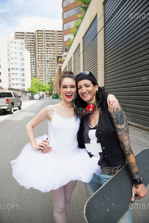 Portrait laughing ballerina and cool female skateboarder hugging in urban alleyの写真素材 [FYI02308584]
