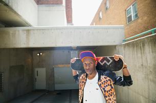 Cool young man holding skateboard at urban parking garage entranceの写真素材 [FYI02308608]