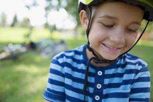 Close up portrait boy wearing bike helmet looking down at parkの写真素材 [FYI02308671]