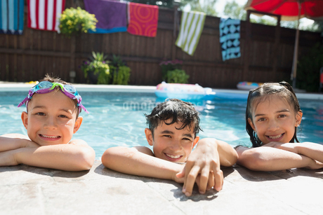 Portrait smiling boys and girl at edge of sunny swimming poolの写真素材 [FYI02308696]