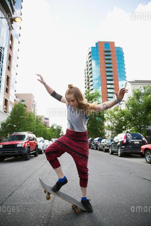 Cool young woman skateboarding in urban streetの写真素材 [FYI02308720]