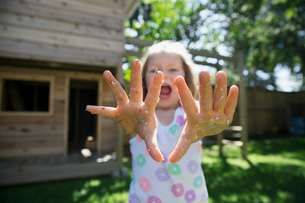 Portrait girl showing messy hands with sprinkles in backyardの写真素材 [FYI02308811]