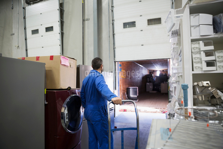 Worker with hand truck preparing to load appliances onto truck at loading dockの写真素材 [FYI02308837]