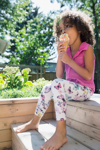 Barefoot girl eating ice cream cone with sprinkles in sunny backyardの写真素材 [FYI02308842]