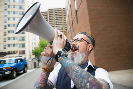 Hipster with beard and tattoos using megaphone in cityの写真素材 [FYI02308844]