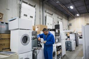 Worker repairing appliances in workshopの写真素材 [FYI02308845]