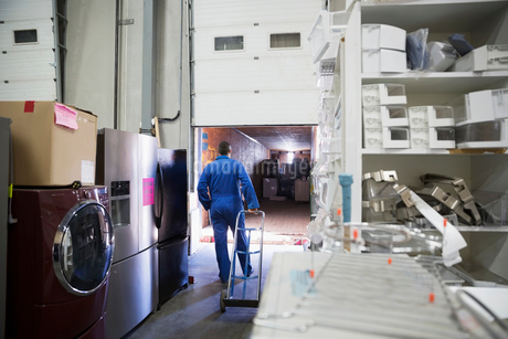 Worker with hand truck preparing to load appliances onto truck at loading dockの写真素材 [FYI02308861]