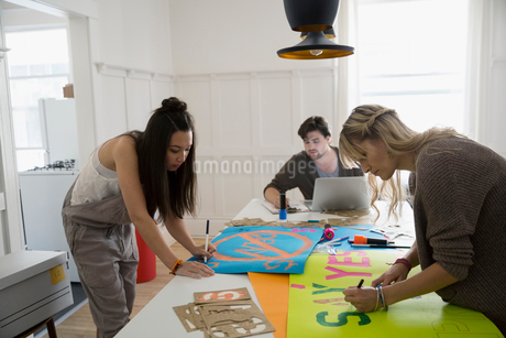 Young activists making posters in dining roomの写真素材 [FYI02308873]