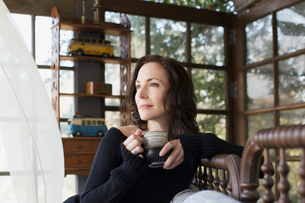 Pensive mature brunette woman drinking coffee looking awayの写真素材 [FYI02308878]
