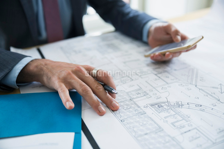 Architect with cell phone reviewing blueprintsの写真素材 [FYI02308903]