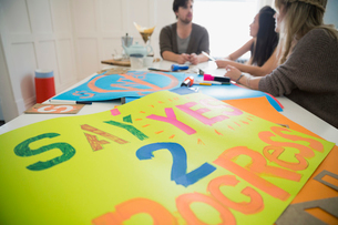 Young activists making posters in dining roomの写真素材 [FYI02308911]