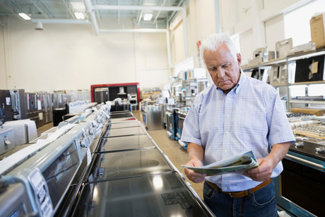 Senior man with sale ad shopping for stove in appliance storeの写真素材 [FYI02308959]